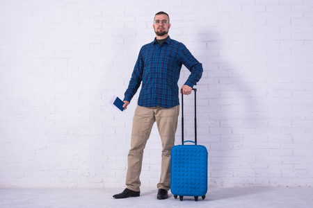 A man with a blue suitcase and a passport near a white brick wall. Vacation, free space. Standard-Bild - 121482685