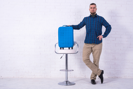 A man with a blue suitcase and passport is sitting on a chair near a white brick wall. Vacation, free space. Standard-Bild - 121482686