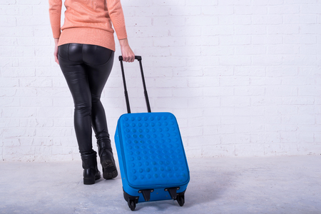 A woman with a blue suitcase near a white brick wall, copy space. Vacation. Standard-Bild - 121482688