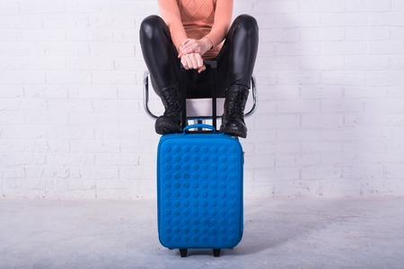 A woman with a blue suitcase is sitting on a chair, free space. Business woman at the airport, vacation. Standard-Bild - 121482689