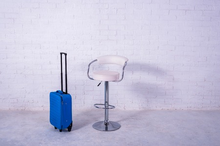 Blue suitcase and high chair near the white brick wall. Free space, travel. Standard-Bild - 121482690