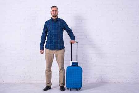 A man with a blue suitcase and a passport near a white brick wall. Vacation, free space. Standard-Bild - 121482783