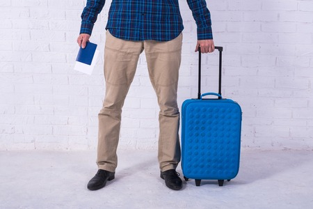 A man with a blue suitcase stands near a white brick wall. Vacation, free space. Businessman at the airport. Standard-Bild - 121482785