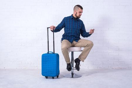 Ein Mann mit blauem Koffer und Reisepass sitzt auf einem Stuhl in der Nähe einer weißen Backsteinmauer. Urlaub, Freiraum. Standard-Bild
