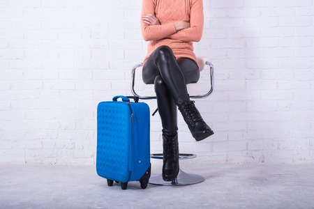 A woman with a blue suitcase is sitting on a chair, free space. Business woman at the airport, vacation. Standard-Bild - 121482787