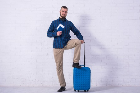 A man with a blue suitcase and a passport near a white brick wall. Vacation, free space. Standard-Bild - 121482790