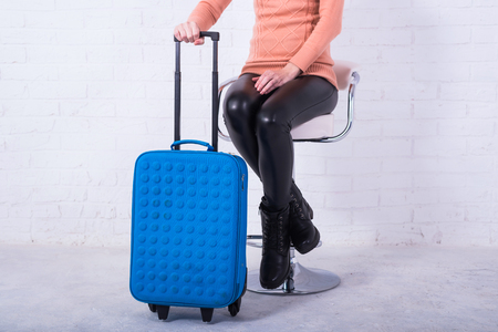 A woman with a blue suitcase is sitting on a chair, free space. Business woman at the airport, vacation. Standard-Bild - 121482794