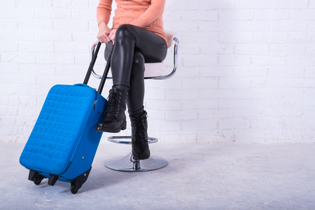 A woman with a blue suitcase is sitting on a chair, free space. Business woman at the airport, vacation. Standard-Bild - 121482796
