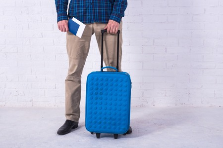 A man with a blue suitcase stands near a white brick wall. Vacation, free space. Businessman at the airport. Standard-Bild - 121482798