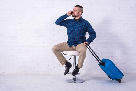 Ein Mann mit blauem Koffer sitzt auf einem Stuhl in der Nähe einer weißen Backsteinmauer und telefoniert. Urlaub, Freiraum. Geschäftsmann am Flughafen.