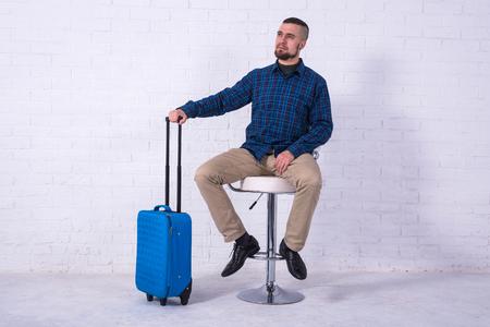 Ein Mann mit blauem Koffer und Reisepass sitzt auf einem Stuhl in der Nähe einer weißen Backsteinmauer. Urlaub, Freiraum.