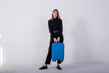 Girl standing with a blue suitcase near a white brick wall. Free space. Business woman is going to the airport. Standard-Bild - 122178116