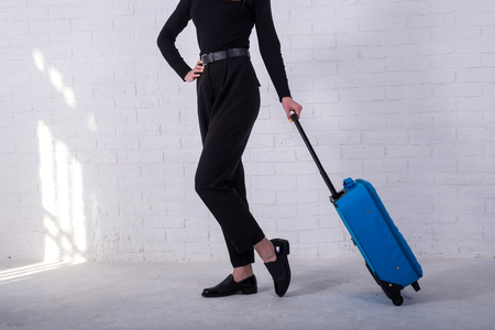 Girl standing with a blue suitcase near a white brick wall. Free space. Business woman is going to the airport. Standard-Bild - 122178117
