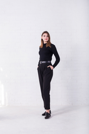 Young brunette in a black sweater and pants standing near a white brick wall, free space. Model posing in the studio. Standard-Bild - 122178119