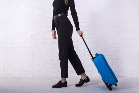 Girl standing with a blue suitcase near a white brick wall. Free space. Business woman is going to the airport. Standard-Bild - 122178120