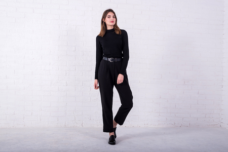 Young brunette in a black sweater and pants standing near a white brick wall, free space. Model posing in the studio.
