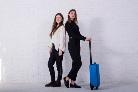 Two young women stand near a white brick wall with a blue suitcase, free space. Preparing to fly on vacation.