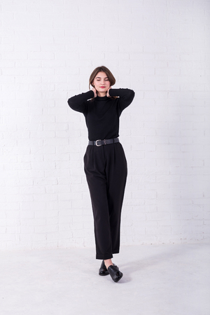 Young brunette in a black sweater and pants standing near a white brick wall, free space. Model posing in the studio. Standard-Bild - 122178161