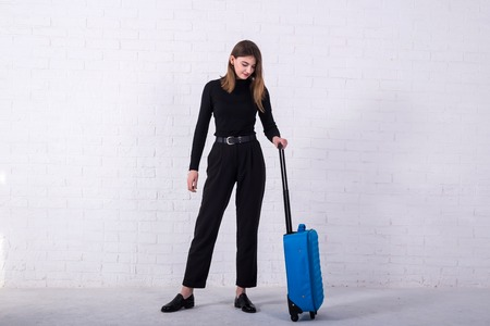 Girl standing with a blue suitcase near a white brick wall. Free space. Business woman is going to the airport. Standard-Bild - 122178162
