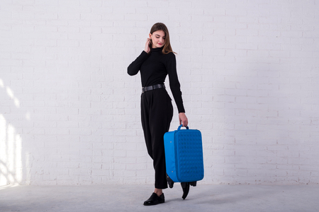 Girl standing with a blue suitcase near a white brick wall. Free space. Business woman is going to the airport.