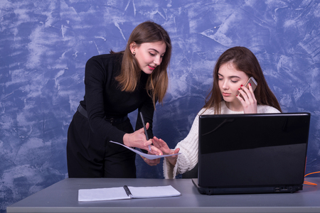 Two businesswomen are discussing a business project behind a laptop. Remote work. Freelancers argue one on one.