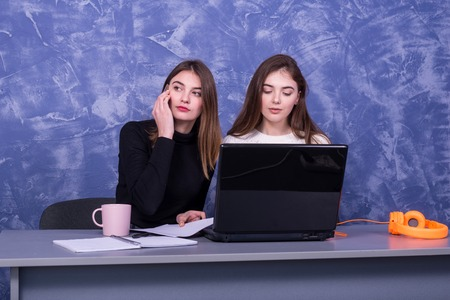 Two businesswomen are discussing a business project behind a laptop. Remote work. Freelancers argue one on one. Standard-Bild - 122178309