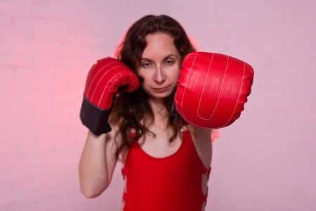Young woman in red boxing gloves on a pink background. Active lifestyle, self-defense Standard-Bild - 122178706