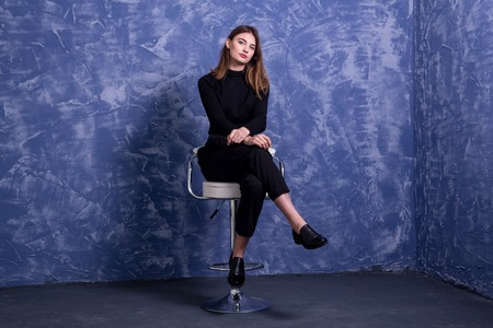 A young woman is sitting on a bar stool against the background of a blue wall, free space. Model posing on a chair. Standard-Bild - 122178739