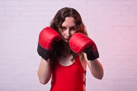 Young woman in red boxing gloves on a pink background. Active lifestyle, self-defense Standard-Bild - 122178745