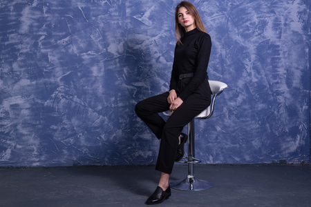 A young woman is sitting on a bar stool against the background of a blue wall, free space. Model posing on a chair.
