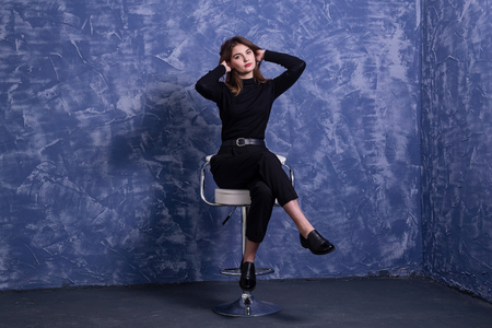 A young woman is sitting on a bar stool against the background of a blue wall, free space. Model posing on a chair. Standard-Bild - 122178770