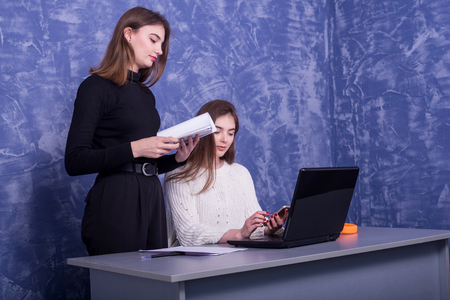 Two young business women are discussing a one-on-one business project. Woman looks at the information on a laptop, remote work. Standard-Bild - 122178775