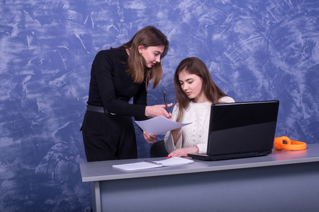 Two young business women are discussing a one-on-one business project. Woman looks at the information on a laptop, remote work. Standard-Bild - 122178779