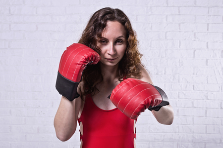 Young woman in red boxing gloves on a white brick background. Active lifestyle, self-defense. Standard-Bild - 122249070