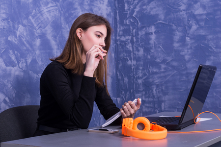 Business woman working at a laptop and writing in a notebook, distant work. Freelancer working. Stockfoto