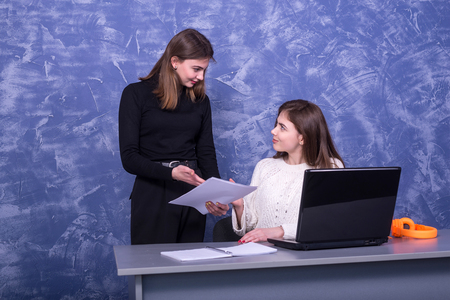 Two young business women are discussing a one-on-one business project. Woman looks at the information on a laptop, remote work.