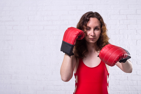 Young woman in red boxing gloves on a white brick background. Active lifestyle, self-defense. Stockfoto