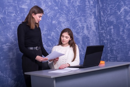 Two young business women are discussing a one-on-one business project. Woman looks at the information on a laptop, remote work. Standard-Bild - 122249163