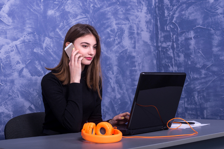 Business woman working at a laptop and talking on the phone, distant work. Freelancer working.