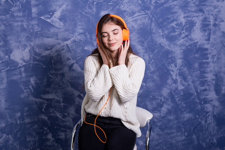 Young beautiful woman listening to music on headphones orange. Girl music lover, relax.