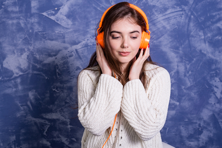 Young beautiful woman listening to music on headphones orange. Girl music lover, relax. Standard-Bild - 122249198