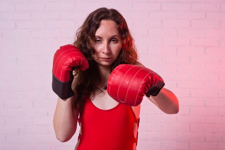 Young woman in red boxing gloves on a pink background. Active lifestyle, self-defense Standard-Bild - 122249679