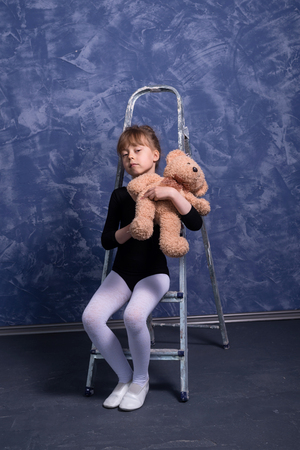 Little girl in the gymnastic swimsuit posing near the stairs, free space. The girl trains in the studio.