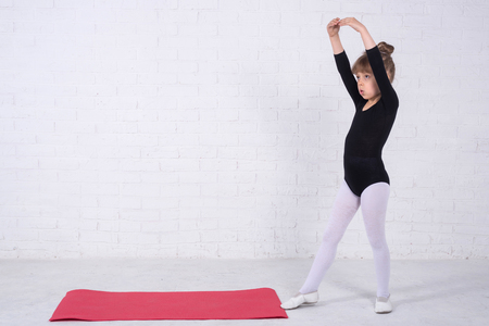 A little girl in a gymnastic swimsuit performing exercises, free space. The girl trains in the studio.