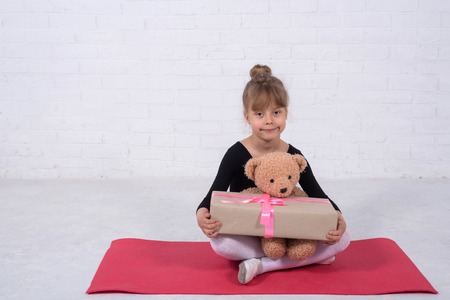 Little girl in the gymnastic swimsuit and with a teddy bear, free space. The girl trains in the studio.