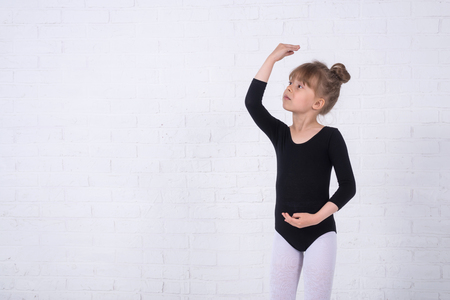 Little girl in the gymnastic swimsuit, free space. The girl trains in the studio.