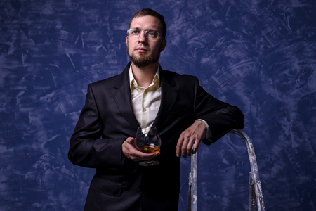 Business man in glasses holding a glass of cognac. Young man on a blue background.