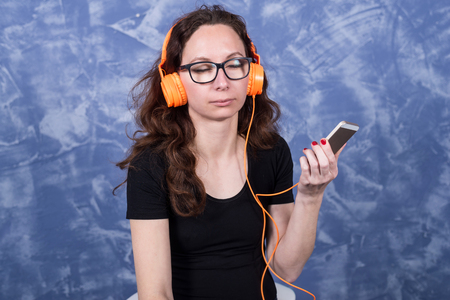 Young woman in glasses listening to music in headphones with the help of a smartphone. Girl in orange headphones with a phone in their hands. Standard-Bild - 122631933