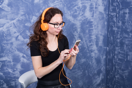 Young woman in glasses listening to music in headphones with the help of a smartphone. Girl in orange headphones with a phone in their hands.