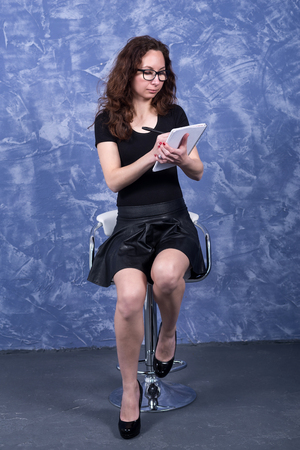 A young woman in black clothes is sitting on a chair on a blue background. Business woman with pen and notepad.